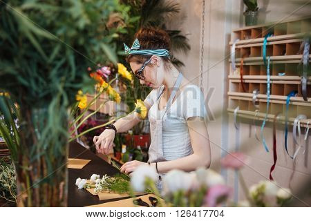 Serious pretty young woman florist standing and making bouquet with white flowers in the shop