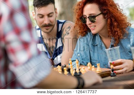 Curly ginger haired female plays chess with male friends at camp in nature