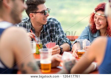 Curly ginger girl and guy make jokes and laugh with friends while playing cards and drinks beer