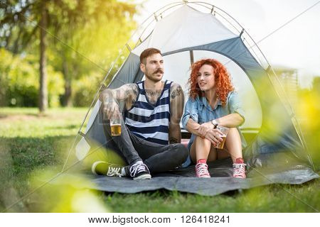 Young man with curly ginger-haired girl rests and drinks beer at summer camp in wood