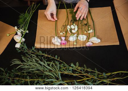 Top view of hands of young woman florist choosing flowers and making boquet on black table