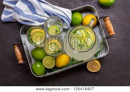 Tray with a refreshing drink and citrus fruits over black textured background. Top view