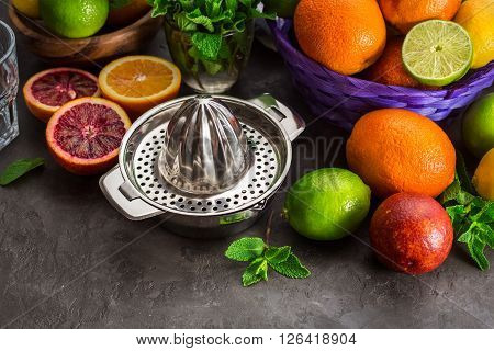 Juicer with different citrus fruits oranges limes and lemons. On the stone table. healthy lifestyle
