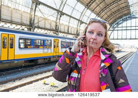 Young woman making a phone call at the central station in Amsterdam the Netherlands