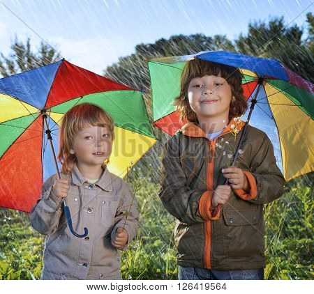 two happy brother with umbrella outdoors