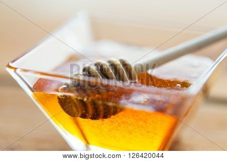 healthy food, eating, natural cosmetics and objects concept - close up of honey in glass bowl and dipper