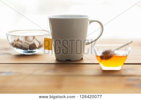 objects and drinks concept - close up tea cup with honey and sugar on wooden table