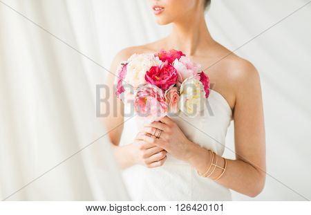 wedding, holidays, beauty, jewelry and luxury concept - close up of beautiful woman or bride with flower bouquet wearing golden ring and bracelet