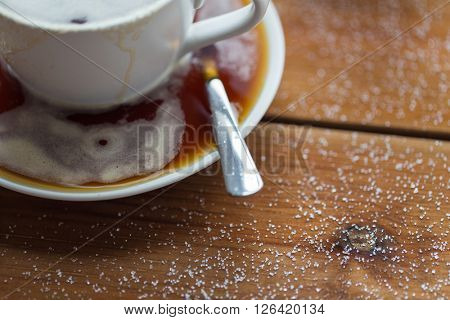 unhealthy eating, object and drinks concept - close up coffee cup and sugar poured on wooden table