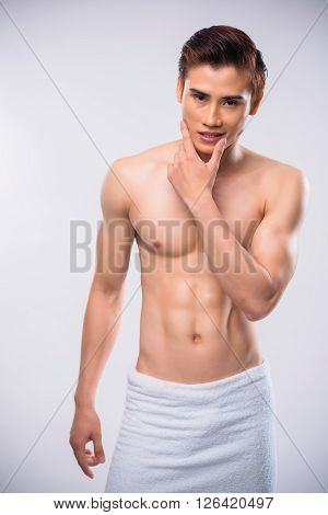 Sensual Asian man in towel, isolated on white