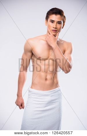 Vietnamese attractive man with towel on his hips looking at camera