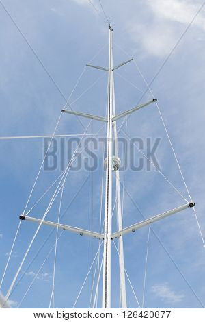 sailing, yachting and travel concept - close up of sailboat mast over blue sky