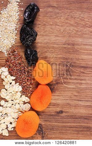 Portion of linseed rye flakes oat bran and dried fruits concept of healthy nutrition and increase metabolism ingredients with dietary fiber copy space for text