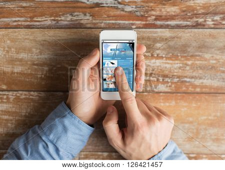 business, mass media, internet people and technology concept - close up of male hands holding smartphone and pointing finger to web page on screen