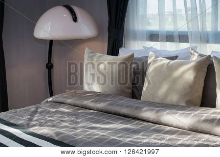 Modern Bedroom With Pillows And White Lamp