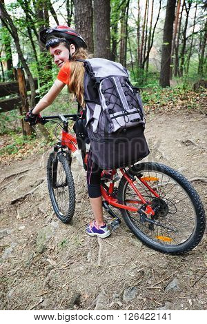 Bikes cycling girl into park. Girl wearing helmet and big backpack