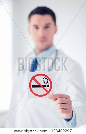 health, medicine and hospital concept - male doctor holding no smoking sign in hands