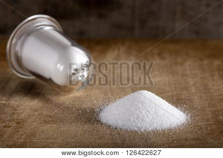 Spilled salt on wood with glass salt cellar in background