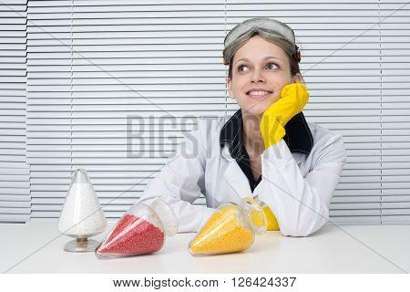 Plastic Pellets. Female Researcher Sitting At A Desk