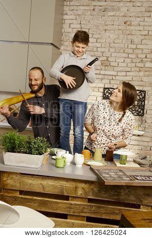 Happy family playing music on kitchen tools, having fun.