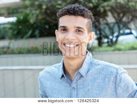 Laughing latin man looking at camera in the city