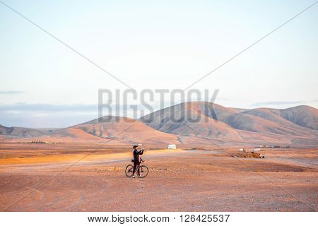 EL COTILLO, FUERTEVENTURA ISLAND, SPAIN - SIRCA JANUARY 2016: Bicycle rider makes picture of a beautiful landscape with mountains on the background near El Cotillo on Fuerteventura island.