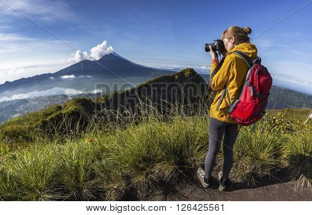 Lady hiker with dslr camera taking a picture of volcano