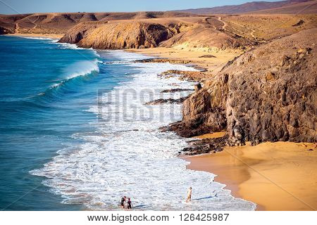 PAPAGAYO BEACH, LANZAROTE ISLAND, SPAIN - SIRCA JANUARY 2016: Crowded beach on the south of Lanzarote island. Papagayo beach is very popular beach on Canary islands