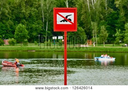 A no swimming danger sign at the beach. there are distance pedal boats ** Note: Visible grain at 100%, best at smaller sizes