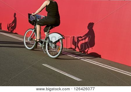 Bicycle road, bike path with part of bike rider in motion. with shadows on the pavement and the wall. focus on the bike. Moscow, Russia, Pushkinskaya embankment.