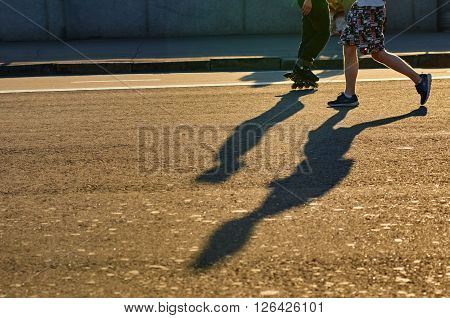 part of body.bound to meet each other runner and roller with shadows. background with the setting sun city. focus on foreground of paving slabs. Moskow Russia, Crimean embankment