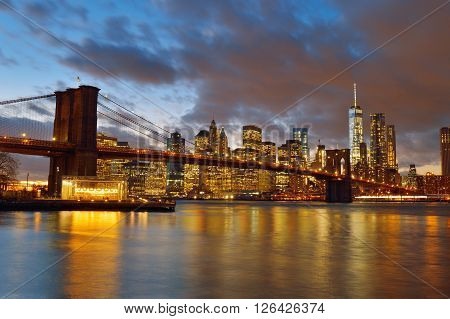 Manhattan skyline with Brooklyn Bridge at night.