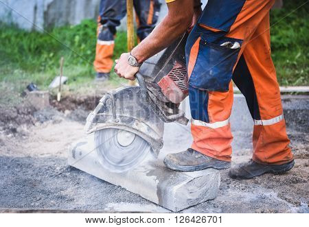 Construction Worker Cutting Concrete Paving Stabs Or Metal For Sidewalk