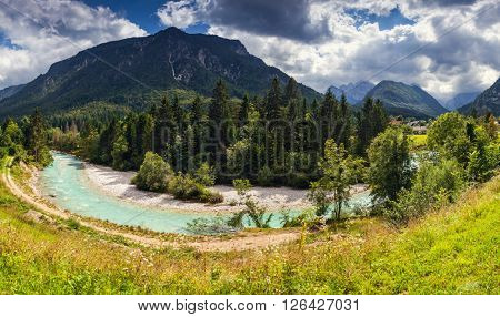 The picturesque view of the mountains that glow under sunlight. River in a green field. Dramatic unusual scene. Location place: Triglav national park, Julian Alps. Slovenia, Europe. Beauty world.