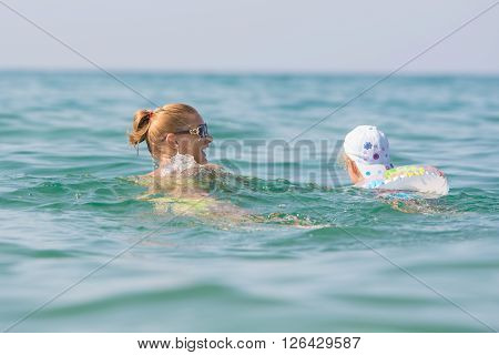 A Girl With A Child Swimming In The Sea