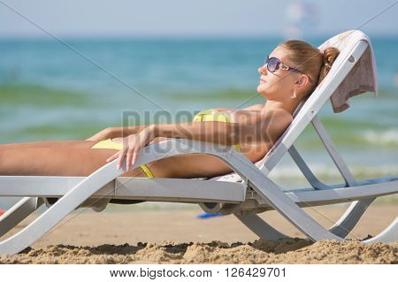 Young Tanned Woman Lying Relaxed On A Sun Lounger On The Beach