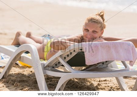 Young girl lying on a sun lounger on the beach with a smile looks in the frame