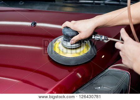 Car detailing series : Closeup of hand polishing red car