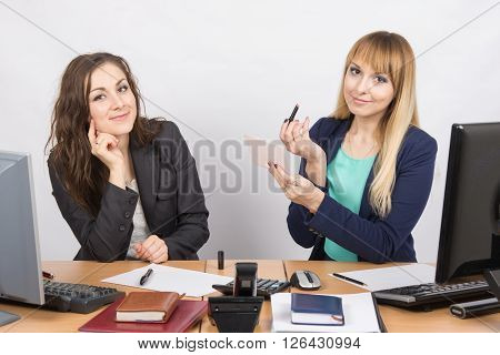 Office Employee Watches As A Colleague Is Going To Make Up Lips At The Desk