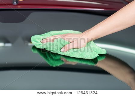 Car detailing series : Closeup of hand using green towel wiping windshield