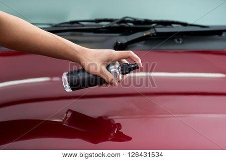 Car detailing series : Closeup of hand  spraying clener on car bonnet