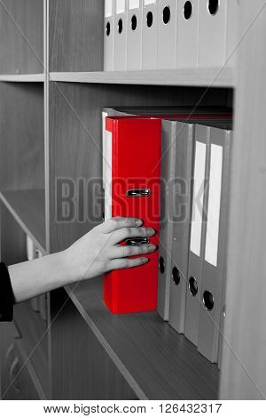 Woman's hand taking a red folder from shelf