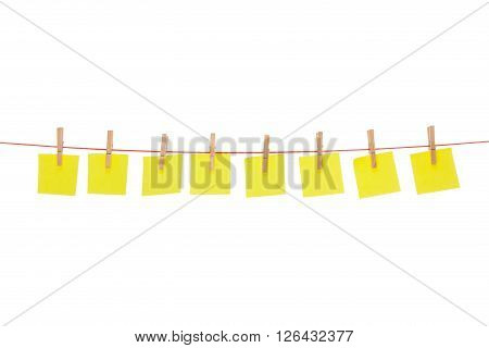 Eight yellow stickies hanged on red rope isolated on white