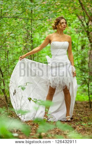 Picture of beautiful bride in white wedding dress at the forest
