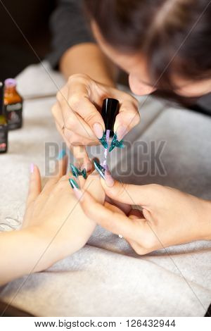 Picture of woman at manicure procedure at nail studio