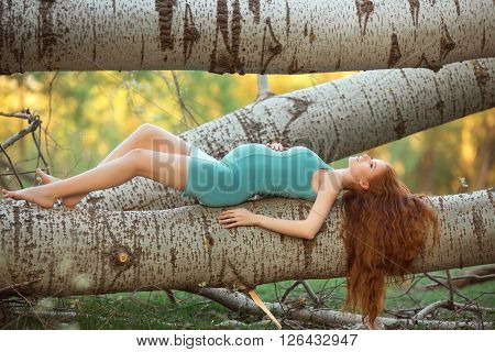Beautiful pregnant fashion model lying and posing among trees, outdoor in nature.