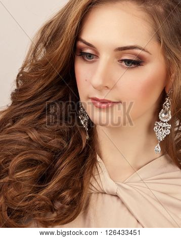Beautiful woman with silver earrings and makeup looking down