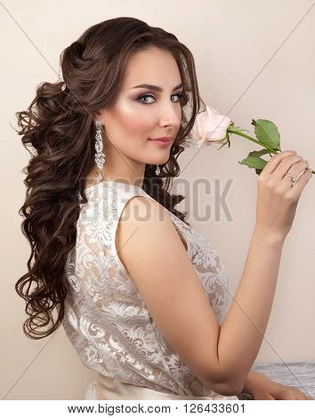 Portrait of beautiful woman with makeup and curly hairstyle in white lace dress
