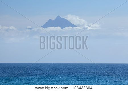 View on the powerful peak of holy mountain Athos above the clouds over the Aegean sea Greece.