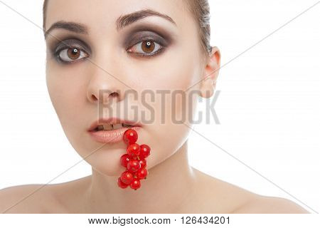 Woman with red currant in her lips isolated on white